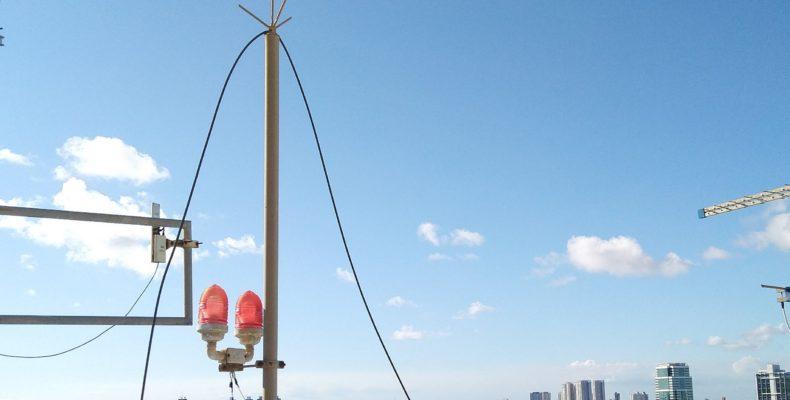 Balizador aéreo em topo de edifício, luz vermelha em cima dos prédios